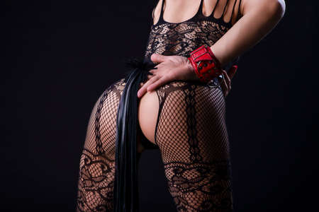 Photo pour BDSM Ideas. Back View of Caucasian Woman in Sexy Lingerie Posing with Leather Lash for BDSM Role Game.In red Handcuffs. Horizontal Image - image libre de droit