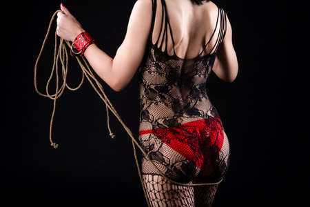 Photo pour Female in BDSM Sexy Lingerie Posing with Rope Accessories for BDSM Play. In red Handcuffs and Net Pantyhose. Horizontal Image Orientation - image libre de droit