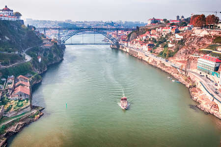 Photo pour Travel Ideas. Traditional Red Tourist Travel Boat Floating in Porto City Across The Douro River in Portugal. Cityscape with Red Rooftops in Background. Horizontal Image - image libre de droit