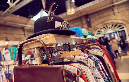 Photo pour Vintage second hand hat and clothes rail showing colourful vintage clothes on coat hangers. - image libre de droit