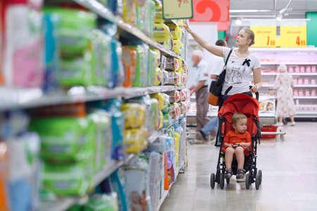 Foto de Mother with her boy in baby carriage in the supermarket - Imagen libre de derechos