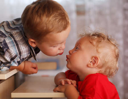 Two little brothers are kissing. Close up portrait. Cute siblings.