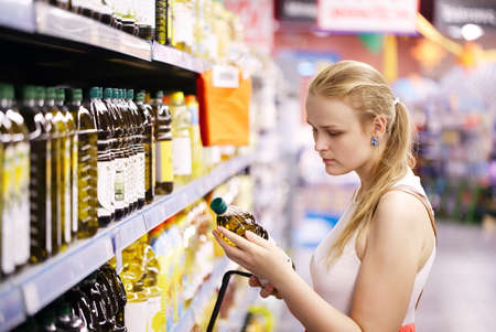 Photo for Young blond woman picking an olive oil bottle from the shelves of a supermarket and reading the label - Royalty Free Image