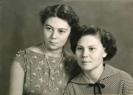 Vintage sepia toned portrait of two attractive young women posing close together looking off to the side of the frame with serious expressions