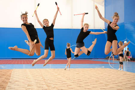 Photo pour Group of four young female gymnasts posing with Indian clubs in a high jump - image libre de droit