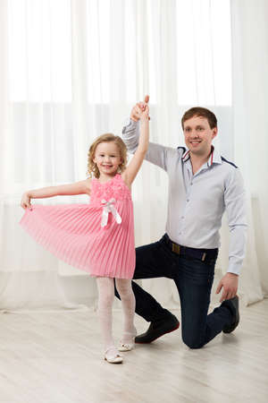 Photo for Father and little daughter dancing. Little princess in pink dress walking around dad standing on knee - Royalty Free Image