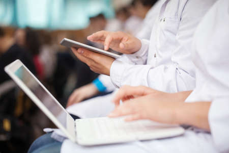 Foto de Male and female medical students or doctors using digital tablet and laptop during the lecture or conference. Focus on the man with pad - Imagen libre de derechos