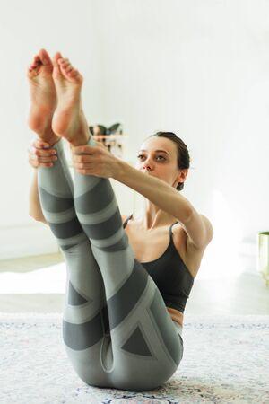 Foto de Young attractive smiling woman practicing yoga in a large, bright room - Imagen libre de derechos