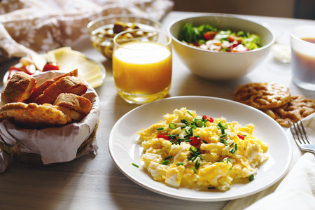 Photo for Breakfast Table with Scrambled Eggs, Fresh Bread, Orange Juice in Morning Sun at Home. Selective focus. - Royalty Free Image