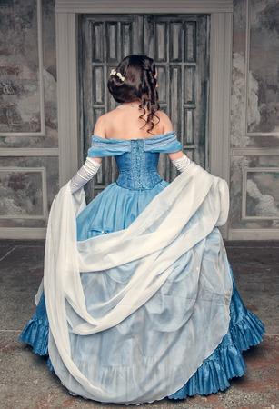 Photo pour Beautiful medieval woman in long blue dress, back - image libre de droit