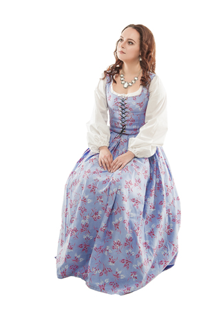 Photo pour Young beautiful woman in long medieval dress sitting isolated on white - image libre de droit