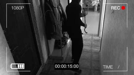 Foto de CCTV camera caught thief with a crowbar broke into the apartment. - Imagen libre de derechos