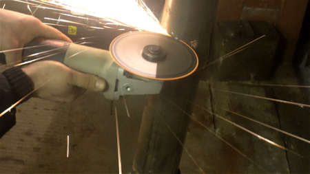 Foto de man sawing metal by grinder,working environment. - Imagen libre de derechos