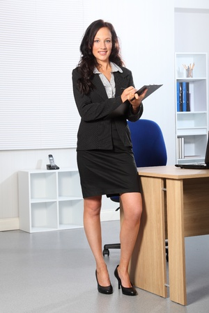 Beautiful young business woman standing in office writing on a clipboard. She has a happy smile on her face.