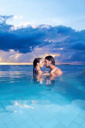 Photo for Romantic couple alone in infinity swimming pool - Royalty Free Image