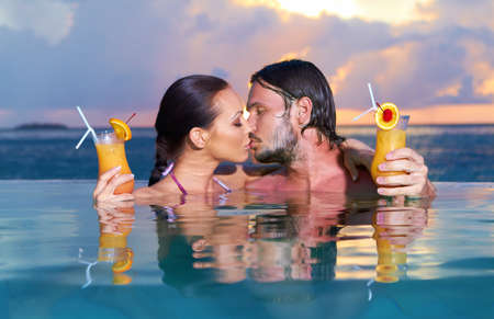 Photo pour Romantic couple alone in infinity swimming pool - image libre de droit