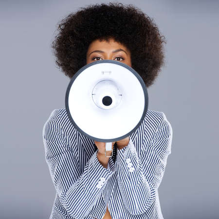 Photo for African American woman speaking into a megaphone making a public announcement with her face partially concealed, square format on grey - Royalty Free Image