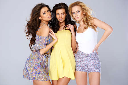 Three sexy chic young women in summer fashion standing arm in arm studio background
