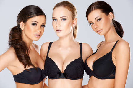 Photo pour Three beautiful young women modeling black lingerie wearing black lacy bras looking off to the side of the frame with charming smiles - image libre de droit