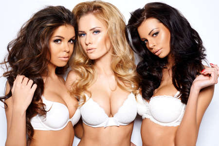 Photo pour Three beautiful sexy curvaceous young women modeling white bras showing off their ample cleavages as they pose arm in arm looking seductively at the camera - image libre de droit