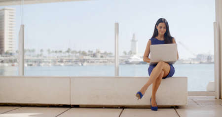 Foto de Attractive young woman sitting on a waterfront bench using a laptop computer sitting smiling at the camera with a thoughtful expression  with copyspace - Imagen libre de derechos