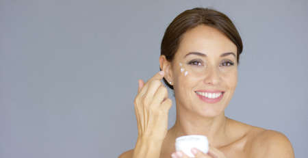 Beauty portrait of a smiling young brunette woman applying dabs of face cream or moisturizer to her face on the cheek bone  over grey