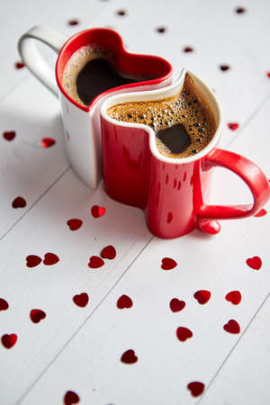 Photo for Two, red and white, heart shaped, connected coffee cups placed on wooden background with sequins. Valentines or love concept. Flat lay, top view. - Royalty Free Image