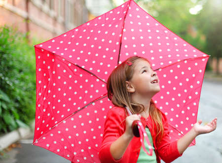 Child with polka dots umbrella wearing red rain boots jumping into a puddle