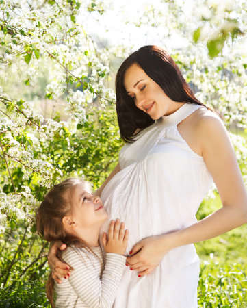 Happy pregnant mother and her little daughter in the spring day