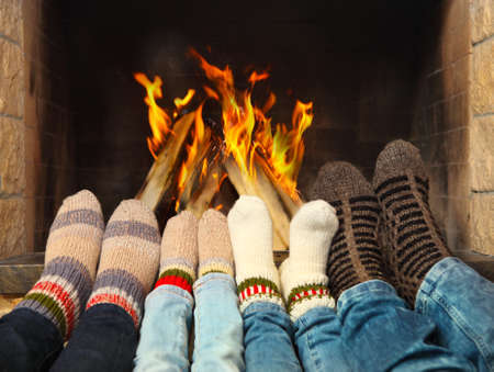 Foto de Feets of a family wearing woolen socks warming near the fireplace - Imagen libre de derechos