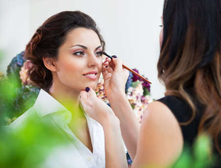 Photo pour Make-up artist doing make up for young beautiful bride applying wedding make-up - image libre de droit