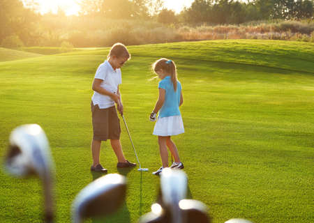Casual kids at a golf field holding golf clubs. Sunset