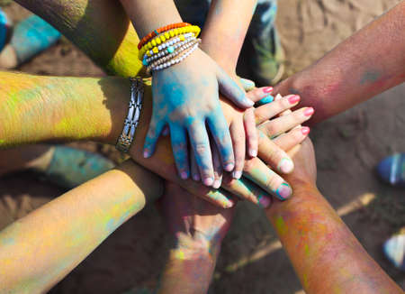 Photo for Friends putting their hands together in a sign of unity and teamwork. Holi colors festival. Friendship concept - Royalty Free Image