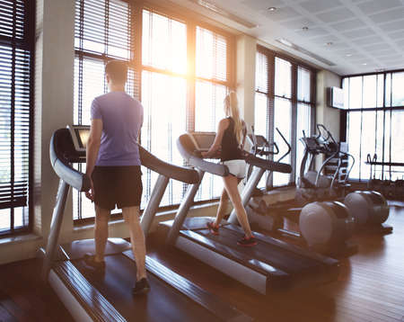 Photo pour Healthy man and woman running on a treadmill in a gym. Sport and health concept - image libre de droit