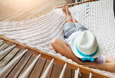 Foto de Lazy time. Man in hat in a hammock on a summer day - Imagen libre de derechos
