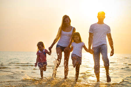 Foto de Happy young family having fun running on beach at sunset. Toned photo. Family traveling concept. No effects - real sun - Imagen libre de derechos