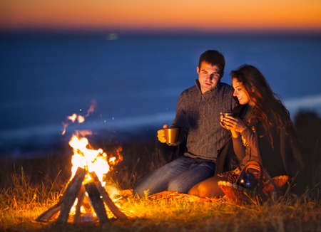 Photo pour Portrait of the happy couple sitting by fire on autumn beach at the night - image libre de droit