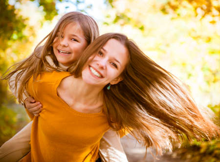 Photo pour Two cheerful sisters playing in the park in warm autumn day - image libre de droit