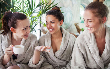 Photo pour Three young happy women drinking tea at spa resort - image libre de droit