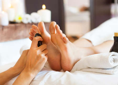 Photo for Massage of human feet by hot stones in spa salon. Close up - Royalty Free Image