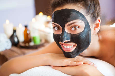 Foto de Young beautiful woman in a mask for the face of the therapeutic black mud. Spa treatment - Imagen libre de derechos