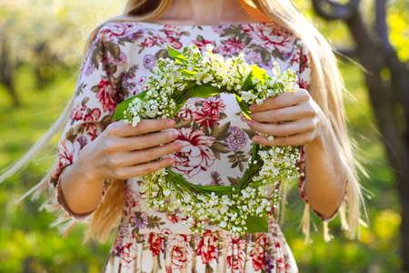 Photo pour Young woman holding wreath from lily of the valley in her hands. Close up - image libre de droit