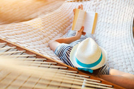 Foto de Lazy time. Man in hat in a hammock with book on a summer day - Imagen libre de derechos