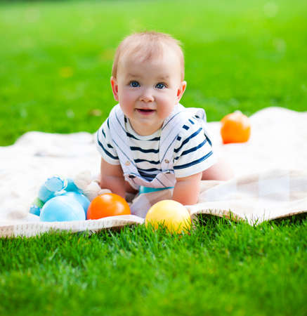 Photo pour Close up portrait of the smiling baby boy playing outdoors - image libre de droit