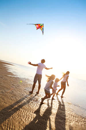 Foto de Happy young family with two kids with flying a kite on the beach - Imagen libre de derechos