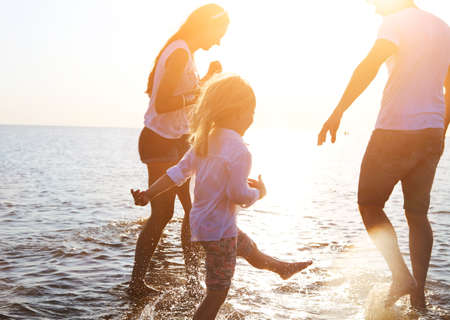 Photo pour Happy young family having fun running on beach at sunset. Family traveling concept - image libre de droit