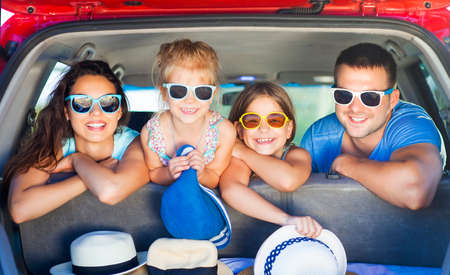 Foto de Portrait of a smiling family with two children at beach in the car. Holiday and travel concept - Imagen libre de derechos