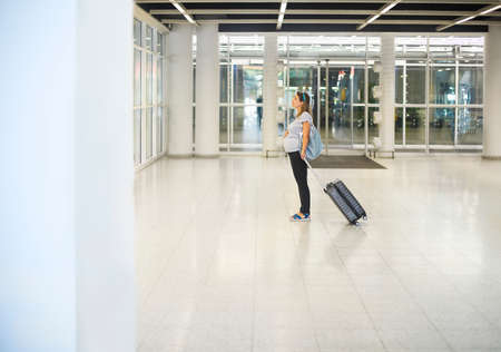 Photo for Young pregnant woman with suitcase at airport or station   - Royalty Free Image