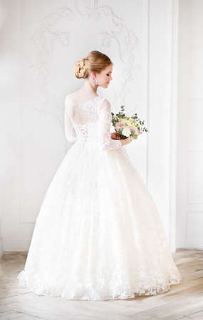 Photo pour Young beautiful blond woman with bouquet posing in a wedding dress  - image libre de droit
