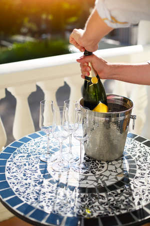 Photo for Champagne bottle and four flutes on the table at outdoor celebration party - Royalty Free Image